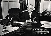 Photo of President Truman with the sign on his desk saying 'the buck stops here'