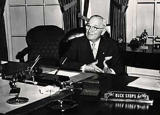 "Buck passing - At the recreation of the Truman Oval Office at the Truman Library in 1959, the former President Truman  poses by his old desk which has the famous ""The Buck Stops Here"" sign."