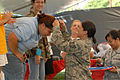 U.S. Air Force Tech. Sgt. Calantha Pickel, a Pacific Command Joint Intelligence Operations Center intelligence analyst, awards a medal to a Special Olympics participant at Joint Base Pearl Harbor-Hickam, Hawaii 101204-F-TP543-248.jpg