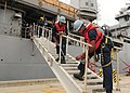 U.S. Navy Boatswain's Mate Seaman Apprentice Anthony Guider and Logistics Specialist Seaman Davonte Meeks secure a ladder as the dock landing ship USS Ashland (LSD 48) arrives at the White Beach Naval Facility 131115-N-NJ145-152.jpg