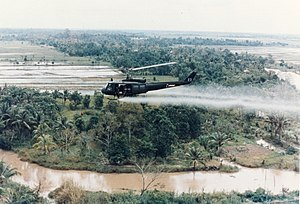 Agent Orange - U.S. Army Huey helicopter spraying Agent Orange over agricultural land during the Vietnam War
