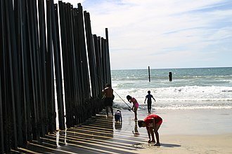 Illegal entry - Family enjoys the beach on the US side of the barrier at the Pacific Ocean in Imperial Beach, California.