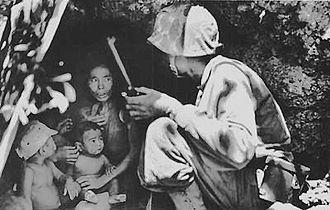Mariana Islands - A U.S. Marine talks a terrified Chamorro woman and her children into abandoning their refuge. Battle of Saipan, 1944.