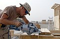 US Navy 030501-N-6077T-003 Builder Constructionman Patrick Dinottia from Binghamton, N.Y., pre-fabricates lumber to construct four hole latrines.jpg