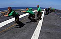 US Navy 041011-N-2143T-015 Aviation Boatswain's Mate Equipmentmen assigned to Air Department, remove old cables from the catapults for replacement and maintenance.jpg