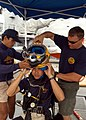 US Navy 050621-N-4104L-015 Boatswain's Mate 3rd Class Daniel Smith, right, secures a MK-21 dive helmet for a Royal Thai Navy (RTN) diver with help from another RTN diver.jpg