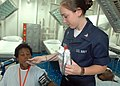US Navy 070812-N-9421C-004 Hospital Corpsman 3rd Class Barbara Linnerooth takes a local man's temperature while he is recovering from surgery aboard the amphibious assault ship USS Peleliu (LHA 5).jpg