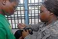 US Navy 070927-N-9562H-036 U.S. Army Sgt. Leonna Thomas, right, a veterinarian technician attached to the Military Sealift Command hospital ship USNS Comfort (T-AH 20), gives an immunization to a dog at the Guyana Society for t.jpg