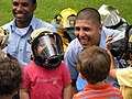 US Navy 071017-N-1923S-001 Sailors assigned to the Crash Division on board NAS Whiting Field, show a pre-schooler at First Steps Christian School how to wear a firefighter's mask.jpg
