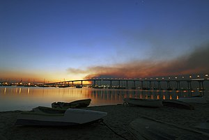 Coronado, California - The sun rises over the San Diego–Coronado Bridge with smoke from the Harris Fire looming overhead