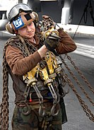 US Navy 080103-N-0455L-006 Aviation Machinist's Mate Airman Tommy Allen transports several tie-down chains across the flight deck aboard the Nimitz-class nuclear-powered aircraft carrier USS Harry S. Truman (CVN 75)