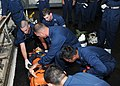 US Navy 110718-N-UE250-022 Sailors assigned to the submarine tender USS Frank Cable (AS 40) strap a training dummy into a stretcher during a medica.jpg