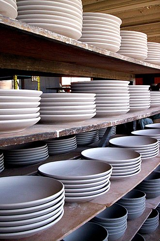 Plate (dishware) - Unglazed plates (bowls on the bottom shelf) with no lip at a pottery