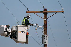 Electrician - A utility electrician/lineman does maintenance on a utility pole.