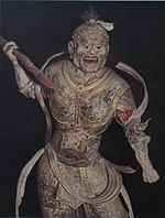 Frontal view of a fierce looking statue dressed in armour and wielding a stick-like object in his right hand.