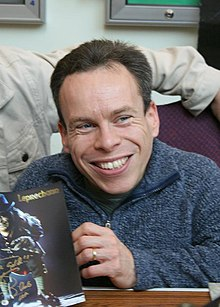 Actor Warwick Davis sits at a table, smiling and holding Leprechaun merchandise