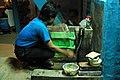 Washing glass mugs by hand in the basement interior of the chaang house, blue walls, blue shirt, motion, green boxes, soap, bricks, hose, spigot, Boudha, Kathmandu, Nepal (5894196563).jpg