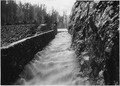 Water overflow rushing between bluff on right and stone wall on left - NARA - 286068.tif