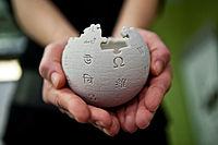 Petit globe Wikipédia présenté au creux de mains anonymes.