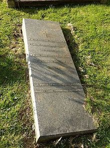 A horizontal gravestone of polished granite, partially sunk on one side