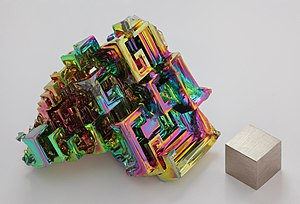 Bismuth - Artificially grown bismuth crystal illustrating the stairstep crystal structure, with a 1 cm3 cube of bismuth metal