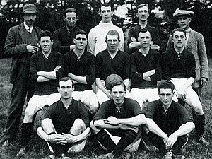 A faded photograph of a posed group of men, outdoors. At the front are three men seated on the ground, each dressed in sports clothing, a dark-coloured shirt, white shorts, dark socks and boots. In the middle row five men are sitting on benches, each dressed in sports clothing. Standing at the back are two men, weating hats and coats, and three men in sports clothing.