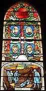 Photographie en couleurs d'un vitrail représentant des portraits surmontant une scène de guerre.