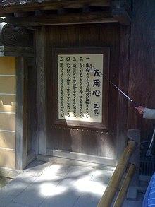 Табличка с китайскими иероглифами, написанными вертикально.  На них указателем указывает мужская рука.