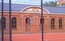 Städtische Turnhalle mit ehemaligem Feuerwehrdepot, zugehörigem Turnplatz mit Lindeneinfassung, natursteingepflasterter Zuwegung, Torpfeilern und westlicher Umfassungsmauer