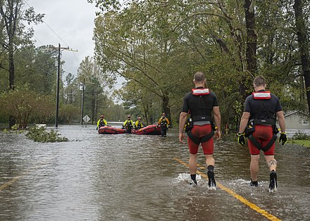 A photograph of two men walking on a flooded street towards a group of men in rafts in the background