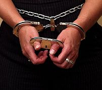 A model wearing both thumbcuffs and handcuffs.