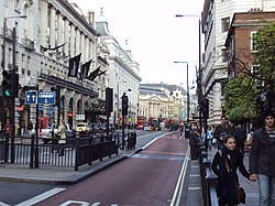 Street picture of Piccadilly with bus lane, road signs and the Meriden Hotel. Piccadilly circus is in the background