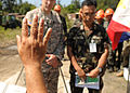A Filipino priest blesses the construction plans for a footbridge before U.S. Army Lt. Col. John Garrity, left, and Philippine army Lt. Col. Henry Bellan, the deputy commanders of Joint Civil Military Operations 130318-N-VN372-048.jpg