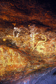 Wall of a cave covered in faded, earthy-coloured figures