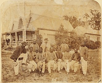 Aboriginal cricket team with captain-coach Tom Wills, December 1866. In the background is the original MCC pavilion, built in 1854. Aboriginal cricket team at MCG in 1867.jpg