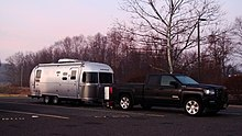 A modern Airstream, 2016 Flying Cloud 23D travel trailer shown with tow vehicle, GMC Sierra