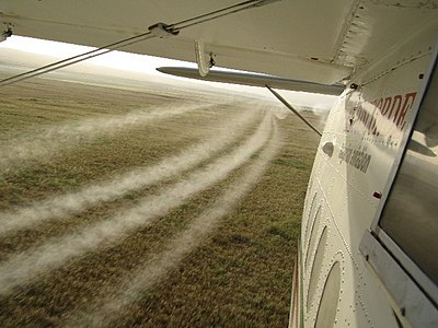 Flying low to the ground, an airplane sprays pesticide on wheat crops in the northern Iraqi province of Dahuk. The spraying was part of the Ministry of Agriculture's Operation Barnstormer.