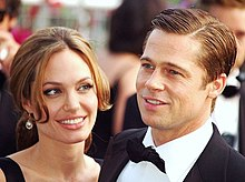 A Caucasian man and woman in the foreground of the image, while others are visible behind them. The woman has brown hair, which is tied back. The man his dark brown hair parted. He is wearing a black suit and bow-tie with a white shirt.