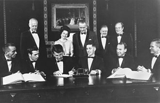 Wally Schirra - Schirra (sitting 3rd from left), signing a commemorative document, with his Apollo 7 crewmates, Apollo 8 crew, Charles Lindbergh, First Lady Bird Johnson, President Johnson, NASA Administrator Webb and Vice President Humphrey (1968)