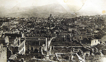 Armenian boroughs of city of Shusha destroyed by Azerbaijani armed forces in 1920 with defiled cathedral of Holy Savior on background.jpg