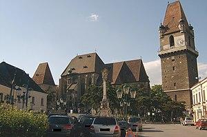 Der Turm rechts weist einen auskragenden Wehrgang auf, im Zentrum die Pfarrkirche