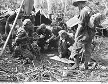 A group of soldiers receive orders prior to a patrol