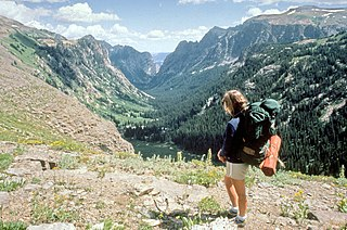 Woman with backpack overlooking a mountain valley