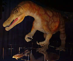 Replica dinosaur and fish in a darkened room