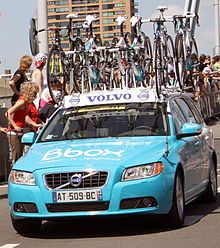 A powder blue automobile with several bicycles attached to its roof. Spectators at the roadside are looking behind the car to something out of the frame.