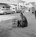 Bejaarde man met handelswaar in banenendozen langs de kant van de weg, Bestanddeelnr 255-3529.jpg