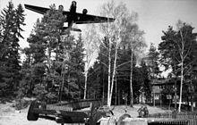 Ein Schwarzweiss-Foto eines dreimotorigen Flugzeuges, das über Bäume fliegt. Das Flugzeug wird von vorne und unten betrachtet. Unter den Bäumen steht ein Haus mit drei Leuten, die davor stehen. Ein weiteres Flugzeug sitzt auf dem Boden und wird von hinten rechts betrachtet.