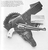 Caption reads: Burnham's sidearm in the Tonto Basin, the Geronimo Campaign, Rhodesia, East Africa, and Mexico was this Remington Model 1875, serial no. 11, in .44–40 caliber. Holster and Rhodesian bandoleer are original; the .44–40 cartridge box bears the stamp of the Rhodesian government. Pistol grips are hippo ivory.