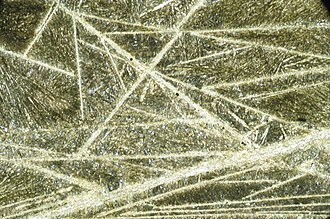 Komatiite - Photomicrograph of a thin section of komatiite showing spinifex texture of pyroxene needle-like crystals