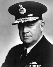 Portrait of man in dark military uniform with pilot's wings on chest, wearing peaked cap with two rows of braid